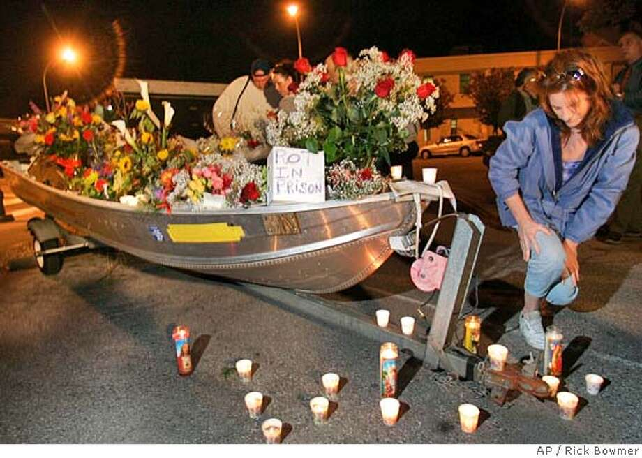 Rena Russ, of Redwood City, Calif., helps build a memorial for Laci Peterson in a boat near a Redwood City, Calif., courthouse Wednesday, Nov. 10, 2004. The boat is similar to the boat Scott Peterson used in the San Francisco Bay on Dec. 24, 2002 that Peterson says he went fishing on. Defense attorney Mark Geragos used this similar boat to conduct experiments. The jury is in the sixth day of deliberations in the case of Scott Peterson. Peterson is charged with two counts of murder in the deaths of hispregnant wife Laci, and the fetus she carried. (AP Photo/Rick Bowmer) Ran on: 11-11-2004  A boat similar to the one Scott Peterson used on San Francisco Bay was parked near the courthouse. Photo: RICK BOWMER