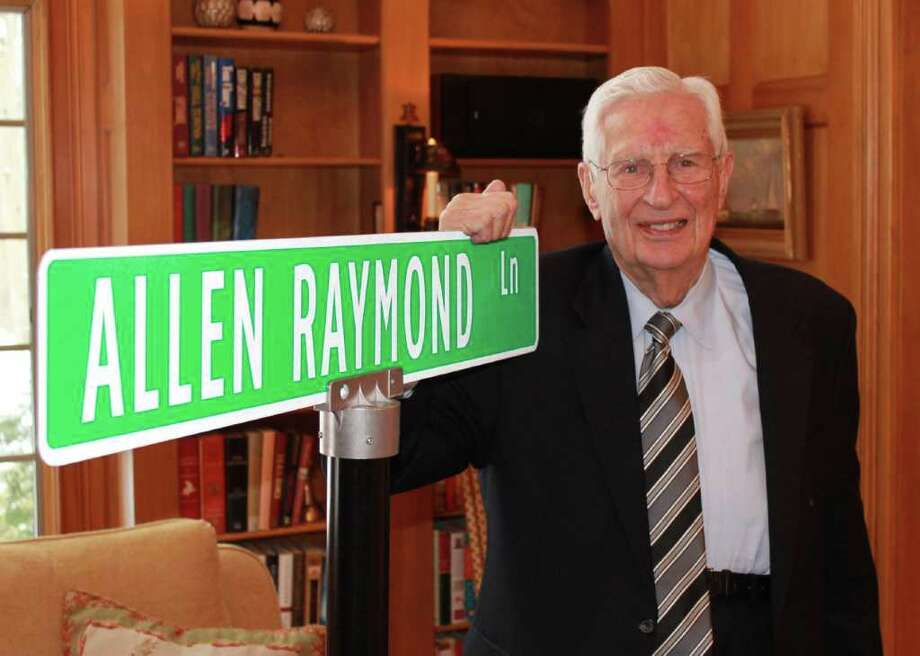 Allen Raymond, trustee emeritus of the Westport Weston Family Y, poses with a facsimile of the street sign that will mark the access road to the Y's Mahackeno Outdoor Center. Naming of the road in Allen's honor was announced Sunday at a party marking his 89th birthday. Photo: Contributed Photo