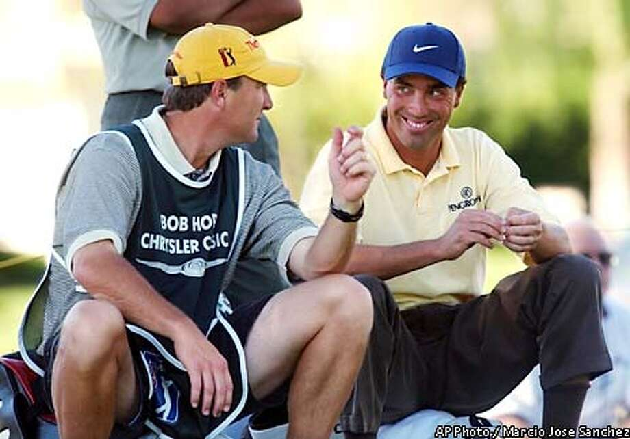 Stephen Ames, right, jokes with his caddie Dean Elliott as he waits to tee off on the 11th hole during the third round of the Bob in La Quinta, Calif., on Friday, Jan. 31, 2003. Ames shot an 8-under-par 64 and is the overall leader at 22 under for the tournament. (AP Photo/Marcio Jose Sanchez) Photo: MARCIO JOSE SANCHEZ