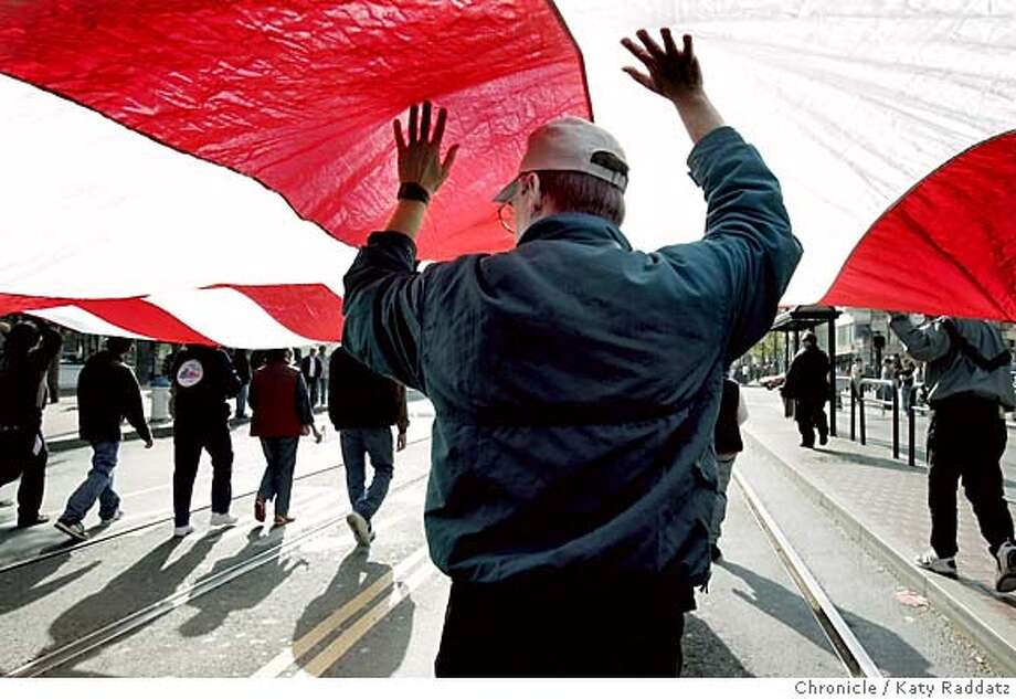 VETERANS08_rad.jpg Veterans Day Parade, San Francisco's 85th annual, marches westward on Market St. SHOWN: Alan Larson from Redwood City marches under a gigantic flag. He said he wants to keep the flag from falling and to show it off. Katy Raddatz / The Chronicle MANDATORY CREDIT FOR PHOTOG AND SF CHRONICLE/ -MAGS OUT Metro#Metro#Chronicle#11/8/2004#ALL#5star##0422455816 Photo: Katy Raddatz