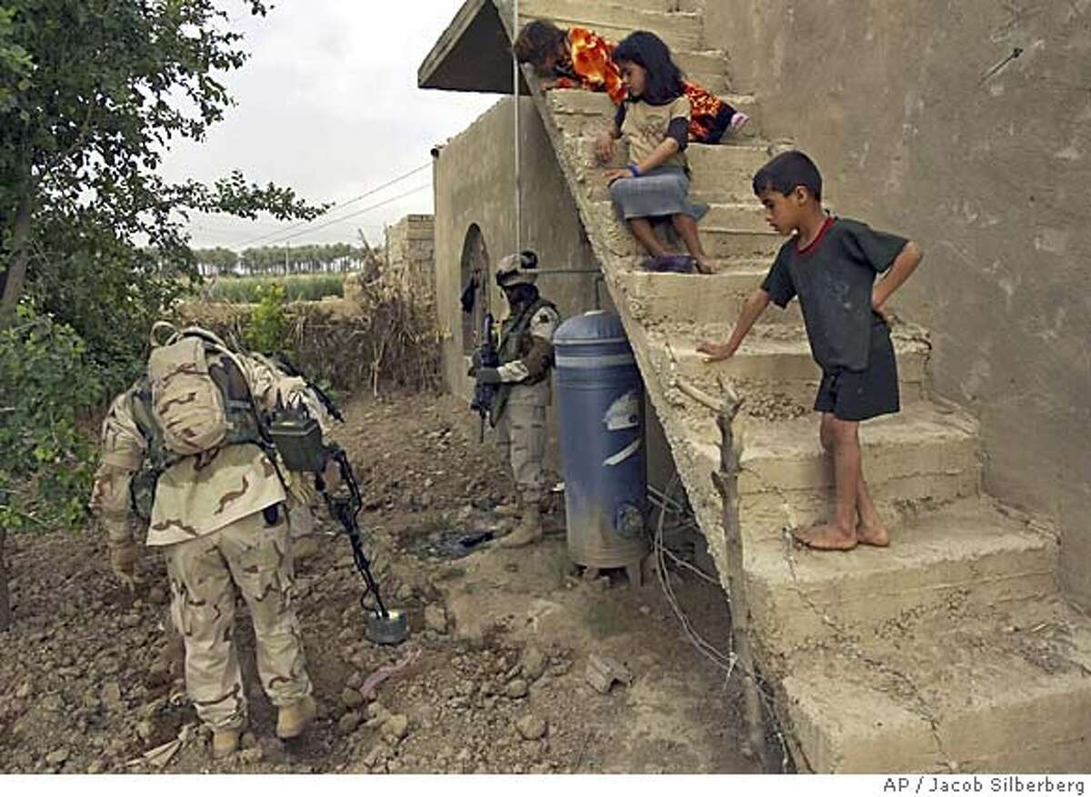 Children watch while US Army Specialist Nathaniel Gainer of Fenton, Michigan, uses a metal detector to search for a buried gun and US Army Staff Sgt. Steve Miller of Mobile, Alabama stands guard behind a house in the outskirts of Baquoba 57 kilometers (35 miles) north of Baghdad, Iraq, Monday, May 2, 2005. Soldiers from the Third Infantry Division, Third Brigade, 2-62 Armor Battalion found an AK-47 based on intelligence from an Iraqi man detained earlier on charges of setting a roadside bomb. (AP Photo/Jacob Silberberg)