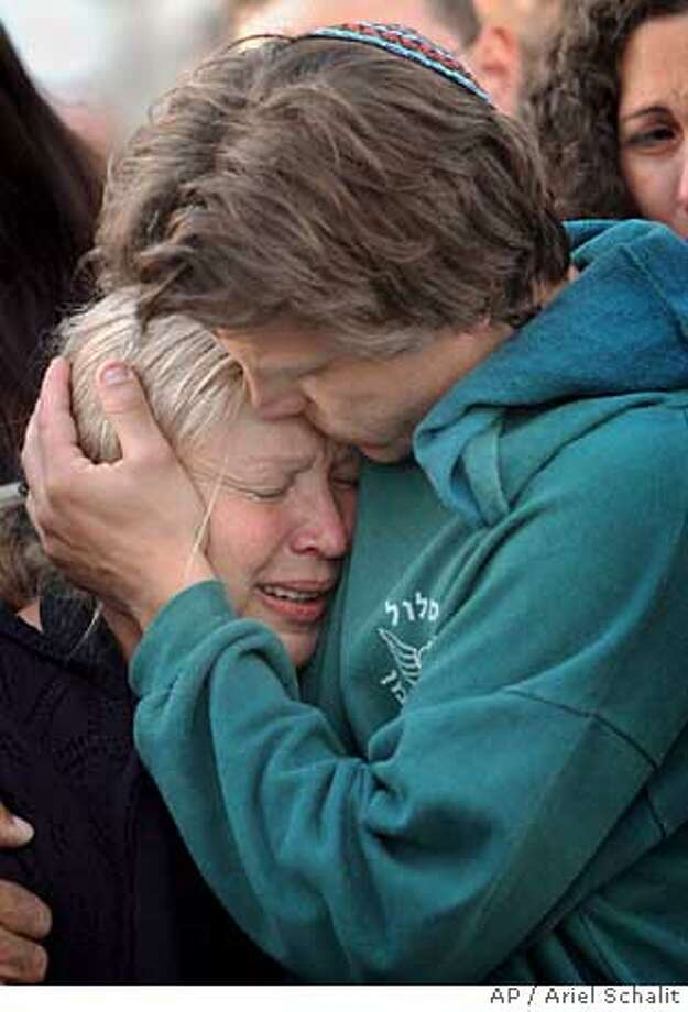 Jan Talasnikov comforts his mother Lea during the funeral of his brother Dan Talasnikov, an Israeli army soldier, at the cemetery of the town of Nir Galim, Israel , Monday May 2, 2005. Talasnikov, 21 , was killed when Israeli troops raided the Palestinian West Bank village of Seideh near Tulkarem before dawn Monday and imposed a curfew. A shootout erupted, leaving a militant and the soldier dead.(AP Photo/Ariel Schalit) Ran on: 05-03-2005  Jan Talasnikov comforts his mother, Lea, at the funeral in the town of Nir Galim for his brother Dan, an Israeli soldier. Ran on: 05-03-2005  Jan Talasnikov comforts his mother, Lea, at the funeral in the town of Nir Galim for his brother Dan, an Israeli soldier. Photo: ARIEL SCHALIT