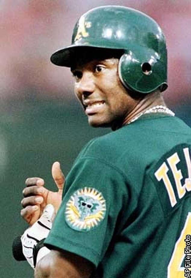 Oakland Athletics' Miguel Tejada stands on first base and winces as he presses on his hand that was hit by a pitch from Texas Rangers pitcher Aaron Sele during the third inning in Arlington, Texas, Tuesday, June 22, 1999. (AP Photo/Bill Janscha) Photo: BILL JANSCHA