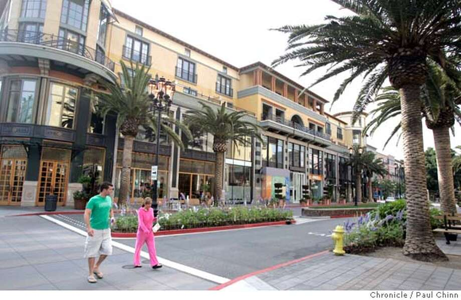 lifestyle28_031_pc.jpg  Shoppers cross a street at the Santa Row shopping district on 4/26/05 in San Jose, CA. In an effort to change the shopping experience, developers are setting up �lifestyle� centers, like Santana Row, which try to mimic your average Main Street, with tree-lined sidewalks and chain stores that look like boutiques. Meanwhile, malls like Valley Fair across the street are trying to stay relevant, undergoing makeovers to seem more modern and inviting.  PAUL CHINN/The Chronicle MANDATORY CREDIT FOR PHOTOG AND S.F. CHRONICLE/ - MAGS OUT Photo: PAUL CHINN