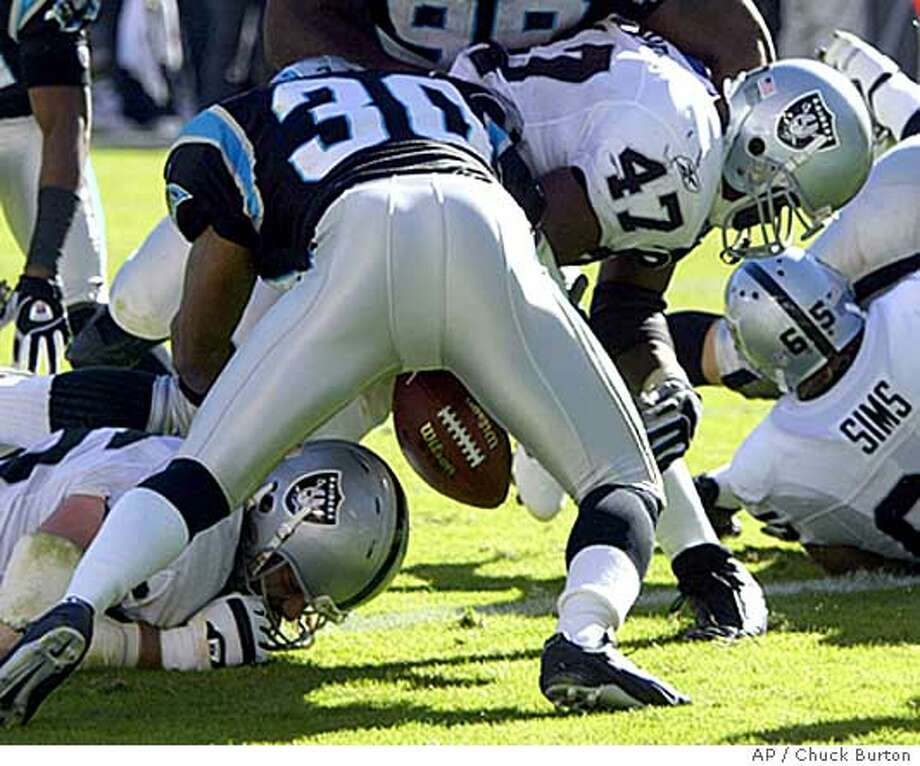 Oakland Raiders' Tyrone Wheatley (47) fumbles the ball after crossing the goal line for a one-yard touchdown as he is hit by Carolina Panthers' Mike Minter (30) during the second quarter in Charlotte, N.C. Sunday Nov. 7, 2004. (AP Photo/Chuck Burton) Photo: CHUCK BURTON