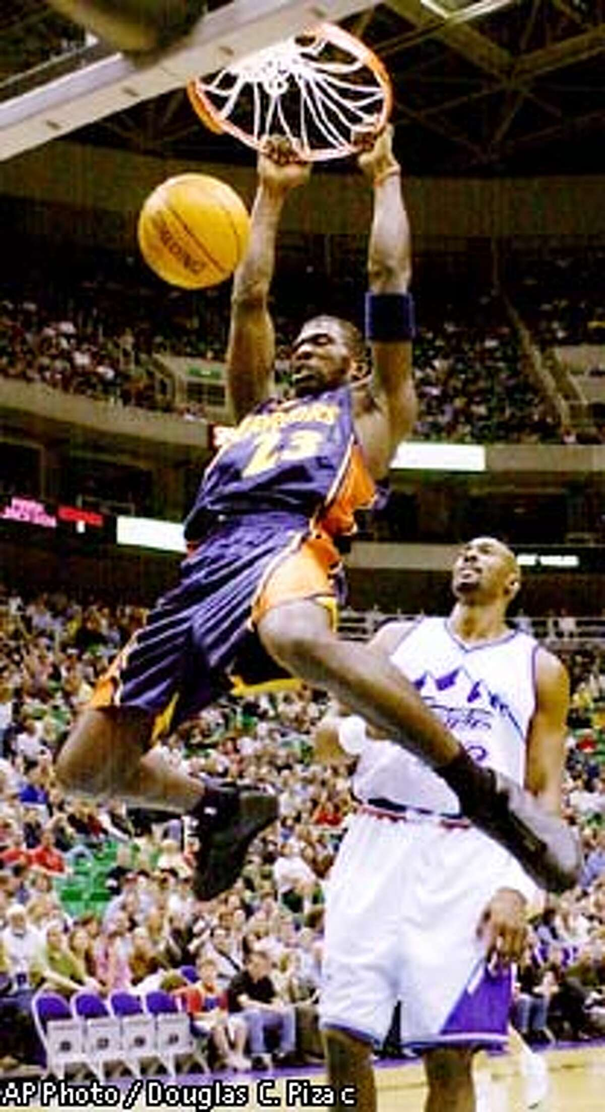 Golden State Warriors guard Jason Richardson (23) dunks on the fast break basket against Utah Jazz forward Karl Malone during the first quarter Friday, Jan. 31, 2003, in Salt Lake City. (AP Photo / Douglas C. Pizac)