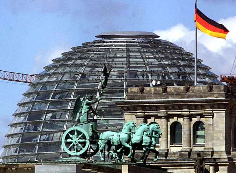 A German flag waves from the top of the Reichstag building in front of the dome designed by British architect Sir Norman Foster in Berlin on Monday, April 19, 1999. The parliament inaugurated its new home in the stately, restored Reichstag Monday, a landmark occasion in the government's return to its prewar capital Berlin. The statue in the foreground is the top of the Brandenburg Gate. (AP Photo/Michael Probst) DIGITAL CAMERA IMAGE Travel#Travel#Chronicle#11/07/2004#ALL#Advance##0422449705 Photo: MICHAEL PROBST