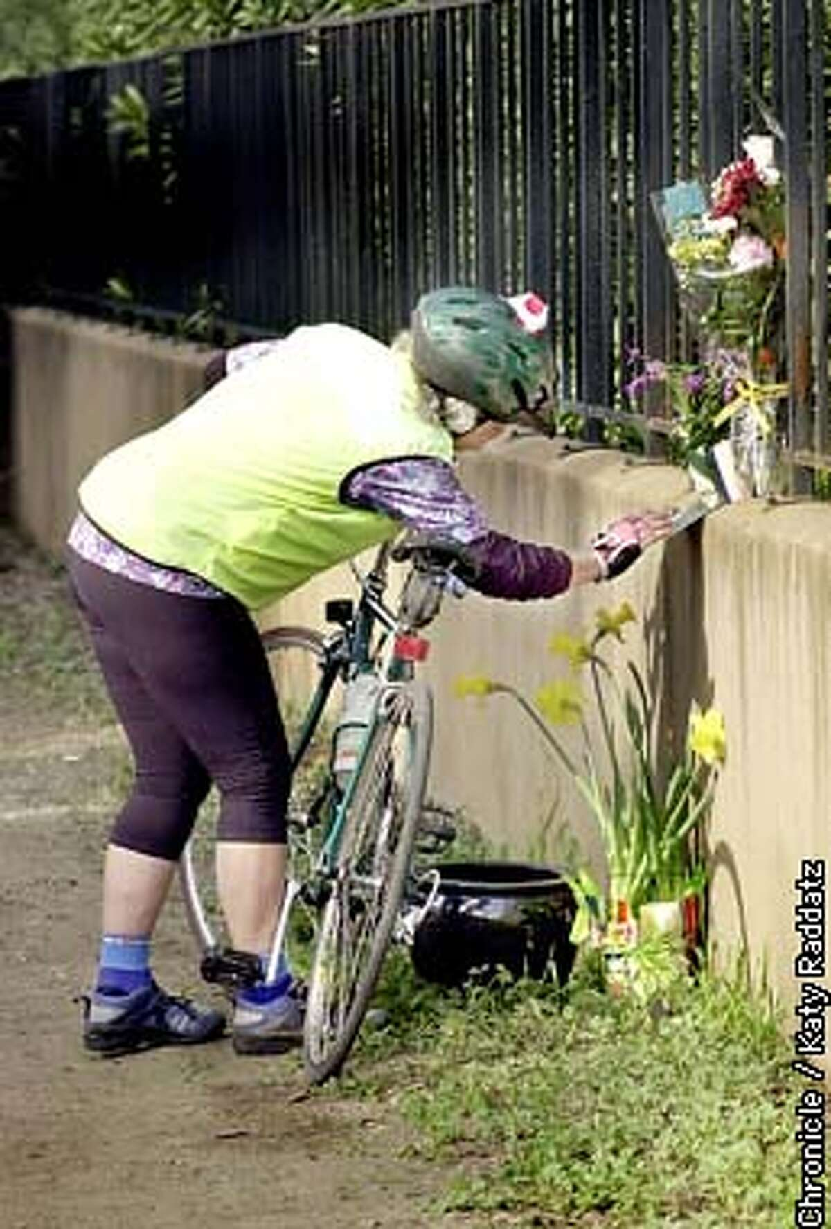 PHOTO BY KATY RADDATZ--THE CHRONICLE Follow up story to the hit-and-run death of Amy Malzbender of Palo Alto. SHOWN: Vivian Wray pauses on her bicycle to read the heartrending note left by friends of Amy on the impromptu memorial on Miranda Ave. in Palo Alto.