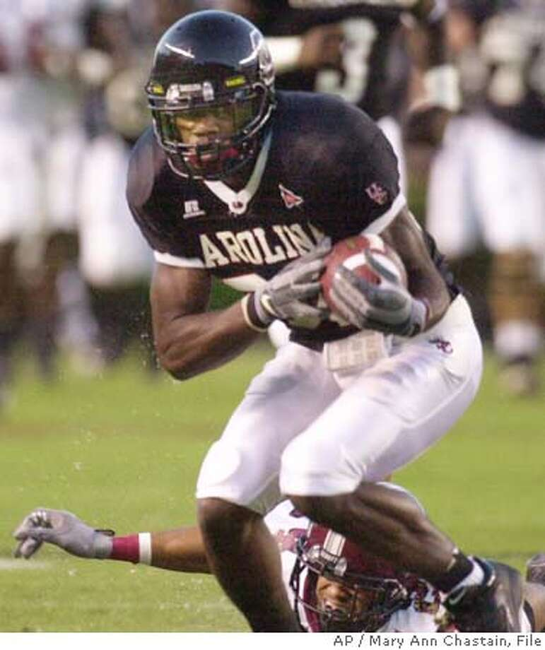 ** FILE ** South Carolina's Troy Williamson, foreground, completes a catch ahead of Troy State defender Freeman White during the first half in this Sept. 25, 2004 photo, in Columbia, S.C. Williamson hadn't even thought much about football until his junior year of high school. But in five seasons he has turned himself into one of the best receiving prospects in Saturday's NFL draft. (AP Photo/Mary Ann Chastain) A SEPT. 25, 2004 FILE PHOTO Photo: MARY ANN CHASTAIN