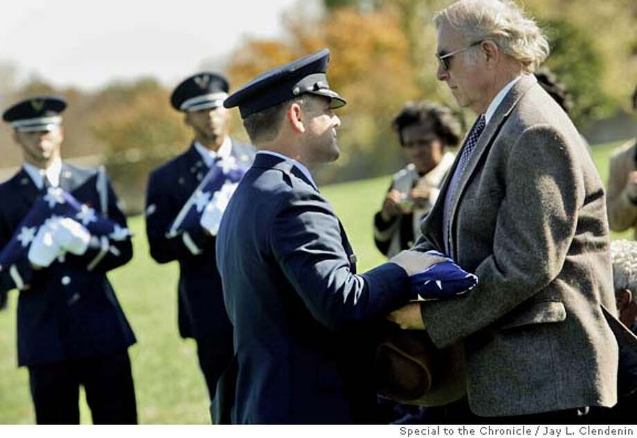 Harding E. (Gene) Smith, Jr. receives a folded flag during a full military burial of his father, USAF Col. Harding E. Smith, at Arlington National Cemetery. Harding E. (Gene) Smith, Jr walks through Arlington National Cemetery after attendiing a full military burial of his father, USAF Col. Harding E. Smith who was lost in 1966 after his plane crashed in Laos. The remains of Smith and his 5 other crew members was recently found. PHOTO BY Jay L. Clendenin/FOR THE CHRONICLE Metro#MainNews#Chronicle#11/6/2004#ALL#5star##0422452954 Photo: Jay L. Clendenin