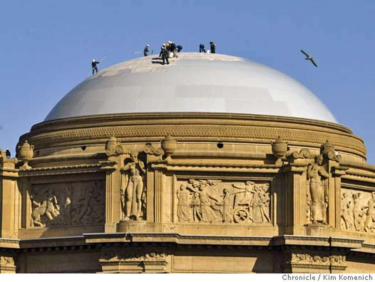 Safely tethered to the building, painters apply a new coat of paint to the dome of the Palace of Fine Arts. Photo by Kim Komenich in San Francisco.