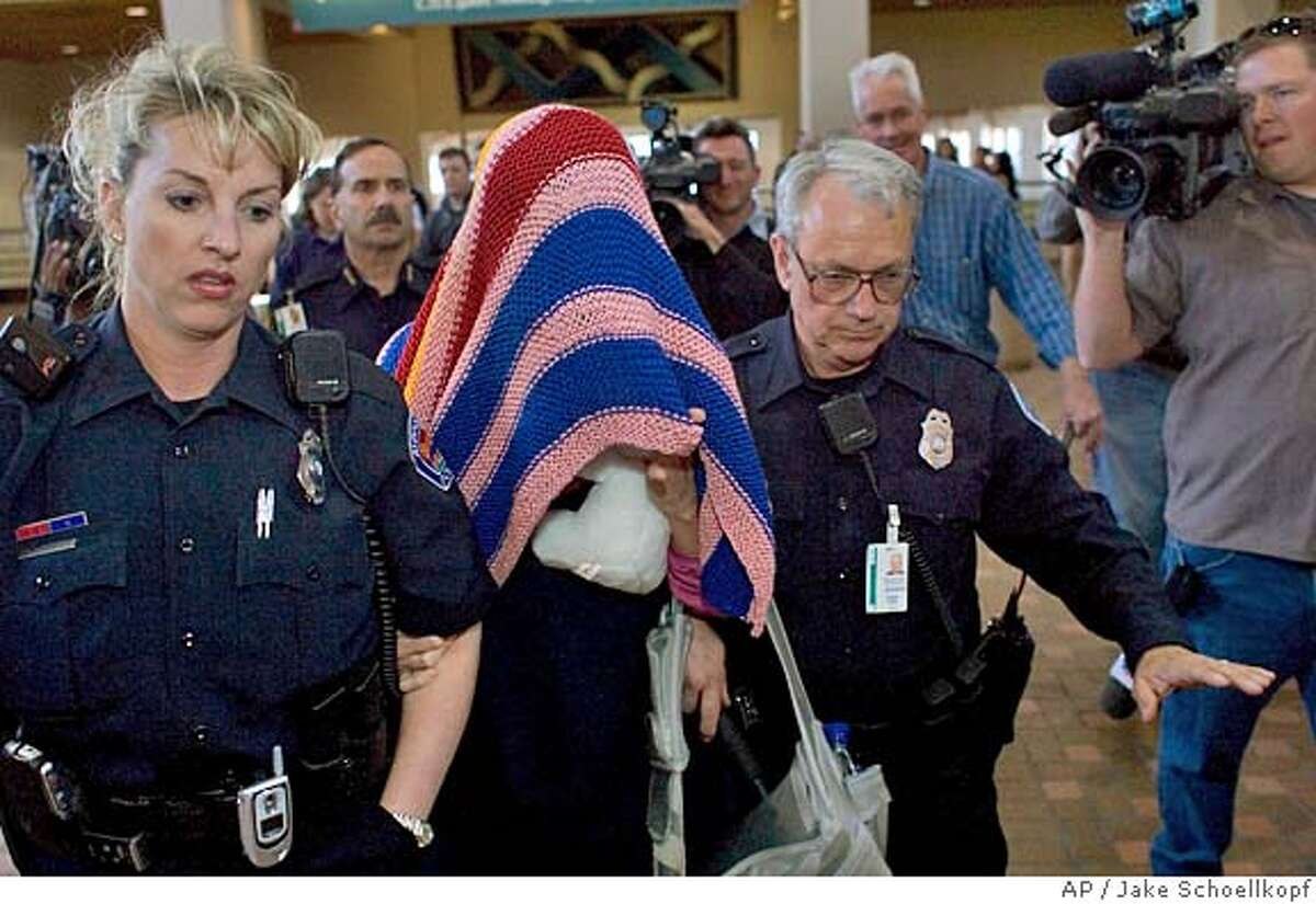 Police officers escort a blanket covered Jennifer Wilbanks through the Albuquerque Sunport, Saturday, April 30, 2005, as she is taken to her flight and back to Atlanta. Wilbanks turned up in Albuquerque late Friday night after she dissapeared last Tuesday, days before her wedding. (AP Photo/Jake Schoellkopf)