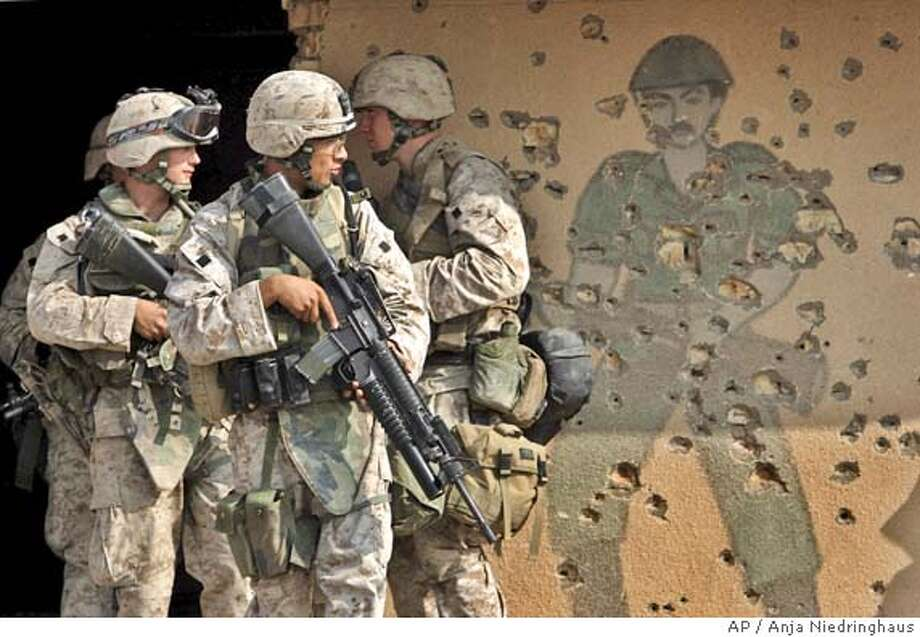 US Marines of the 1st Division pass by a wall painting of an Iraqi Army soldier during training in a former Iraqi army barrack outside Fallujah, Iraq, Thursday, Nov. 4, 2004. U.S. forces are preparing for a major offensive in Fallujah, west of Baghdad, and other Sunni militant strongholds in hopes of curbing the insurgency ahead of January's election. (AP Photo/Anja Niedringhaus) Photo: ANJA NIEDRINGHAUS