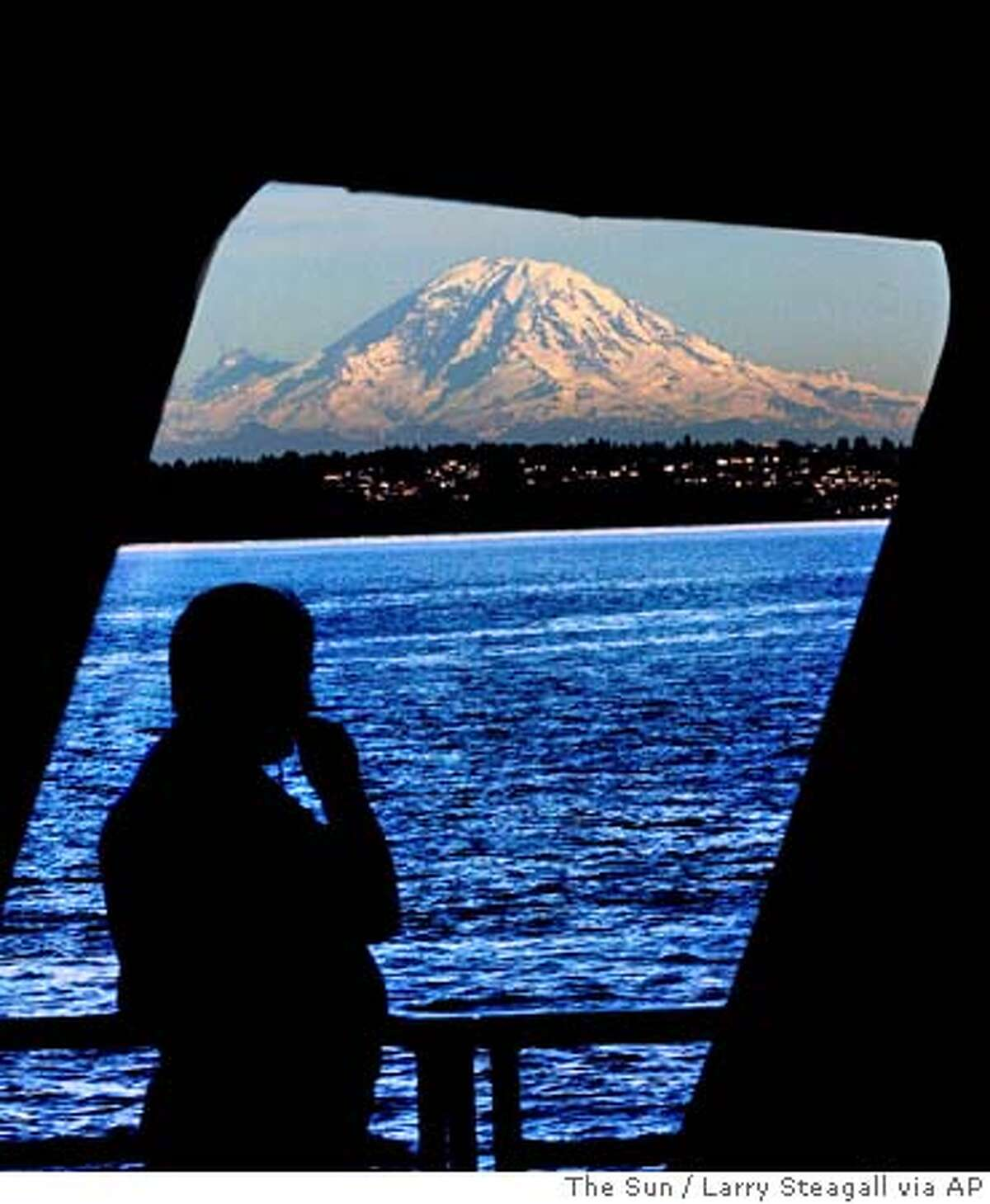 A commuter on the Spokane Auto Ferry from Edmonds to Kingston has a spectacular view of Mount across Puget Sound, on Monday, June 30, 2003. (AP Photo/The Sun, Larry Steagall)