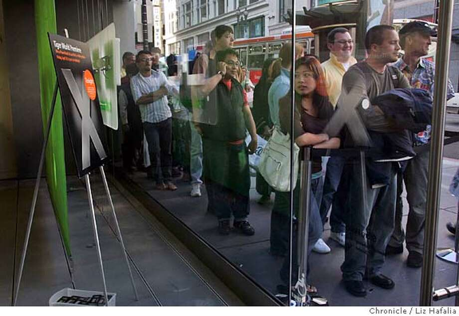 Apple Computer Inc. will be giving away goodies (ie. laptops, ipods) as part of its sales launch of its newest operating system, Tiger. Tammy Chen and her fiancee Mario Ortiz, from San Francisco, have been waiting since 3:00pm. The actual line started at 4:00pm. Shot in San Francisco on 4/29/05. Photo: Liz Hafalia