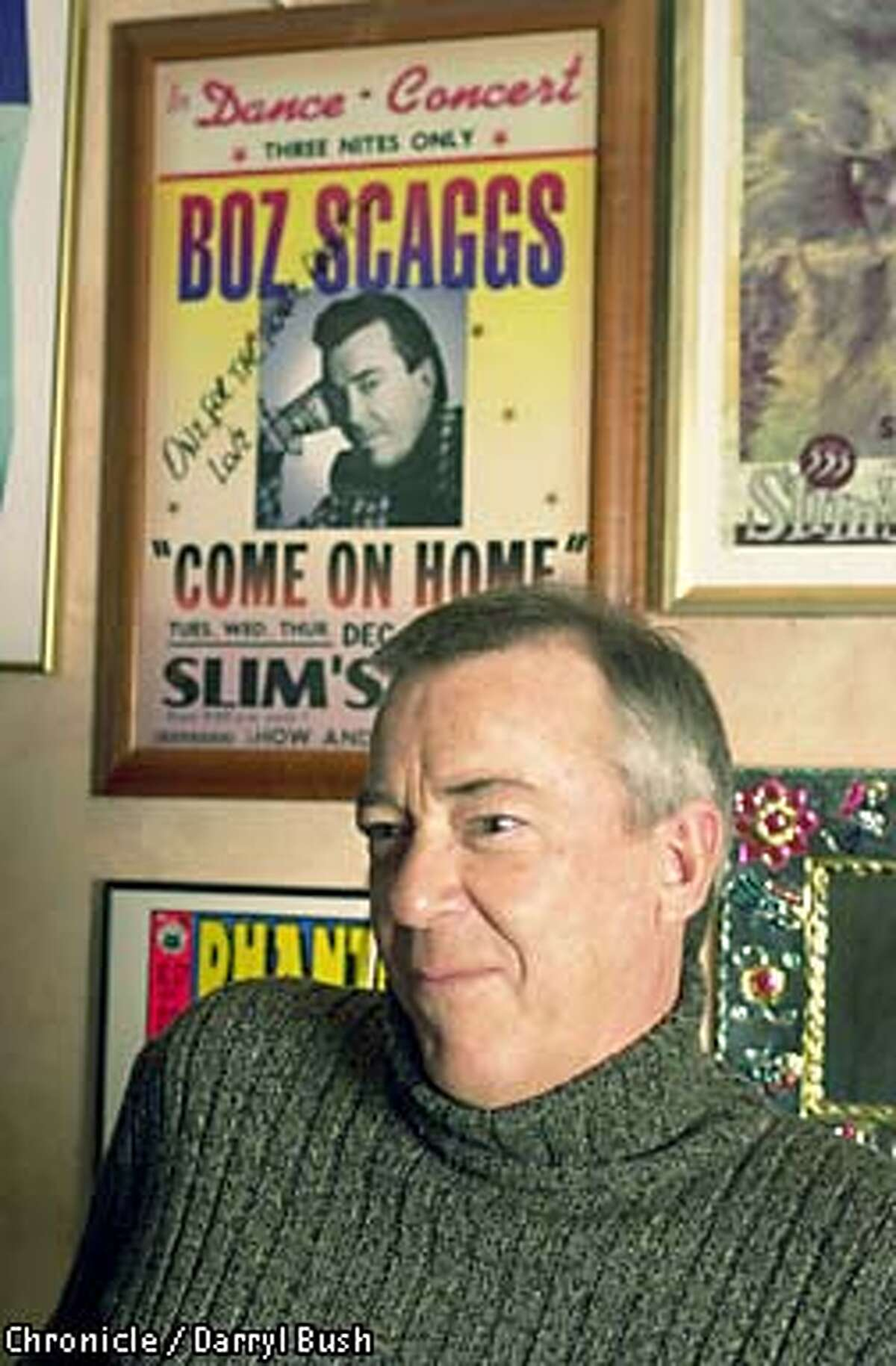 Boz Scaggs with a poster of concert he played in the background, inside the basement office of Slim's nightclub in San Francisco. Chronicle Photo by Darryl Bush