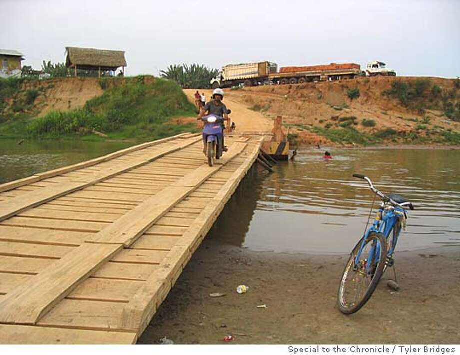Current bridge over the Acre River, which will soon be washed away and later replaced by the big bridge. The photo is taken on the Peru side of the river, with Brazil on the far side. TYLER BRIDGES/ Special To The Chronicle Ran on: 11-05-2004  The current bridge over the Acre River, which connects Peru and Brazil (far side of bridge), will soon be washed away and later replaced by a large new bridge costing $7 million. Environ- mentalists fear that an all-weather highway will lead to further destruction of the Amazon rain forest. Ran on: 11-05-2004