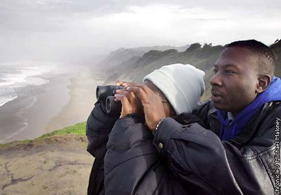 DROWNEDd-C-27JAN03-MT-MJM  At Pomponio State Beach, Remi Daodu (left) and her husband Dada Daodu look out to sea from a bluff overlooking the beach where their son was swept out to sea. A San Leandro family has been searching the beaches off the San Mateo coast for their 16 year old son's body. Kayode Daodu was swept out to sea while playing with friends at Pomponio State Beach last Sunday. The Coast Guard called off it's search on Monday but the family has been searching on it's own every day .  SF CHRONICLE PHOTO BY MICHAEL MALONEY Photo: MICHAEL MALONEY