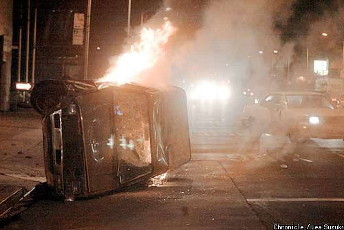 A car burns in Oakland on International Boulevard and 62nd Avenue as fans riot in Oakland after the Raiders lost in the Super Bowl. Chronicle photo by Lea Suzuki