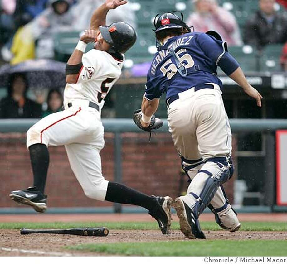 Safe at home. Giants 56- Jason Ellison bends to avoid the tag by Padres catcher- Ramon Hernandez in the 6th inning. Ellison scored on a bases loaded single by J. T. Snow. San Francisco Giants vs San Diego Padres. Giants win 10-3. SBC Ballpark. 4/27/05 San Francisco, Ca Michael Macor / San Francisco Chronicle Photo: Michael Macor