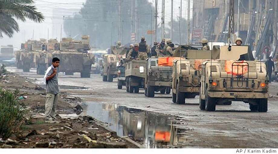 A U.S. Army and Iraqi military convoy passes through after conducting a joint search operation in the Sadr City neighborhood of Baghdad, Iraq Wednesday, Nov. 3, 2004.(AP Photo/Karim Kadim) Photo: KARIM KADIM