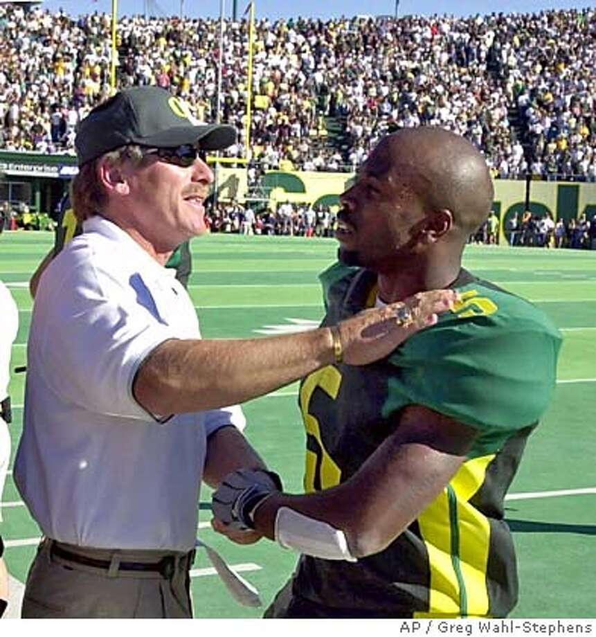 ADVANCE FOR WEEKEND OF OCT. 7-8--FILE--University of Oregon head football coach Mike Bellotti congratulates wide receiver Marshaun Tucker as he comes off the field during their win over UCLA in Eugene, Ore., Sept. 23, 2000. This season the Ducks have blown away all expectations, going from a team that struggled to score against Nevada to knocking off Top 10 powers UCLA and Washington.(AP Photo/Greg Wahl-Stephens) DIGITAL IMAGE Sports#Sports#Chronicle#11/3/2004#ALL#5star##422087315 Photo: GREG WAHL-STEPHENS
