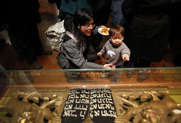 Helen Bobell, of Oakland, shows her son Kai, 22 months, a 20th century Torah Ark pediment at the re-opening of Magnes Museum in Berkeley, Calif., Sunday, January 22, 2012. Photo: Sarah Rice, Special To The Chronicle