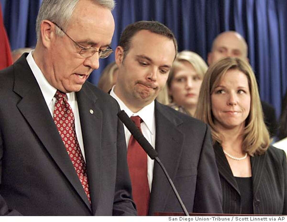 San Diego Mayor Dick Murphy, left, announces Monday, April 25, 2005, his resignation as mayor, effective July 15, 2005, at City hall in San Diego. Murphy resigned amid a widening federal investigation into the handling of the city's deficit-riddled pension fund. Next to Murphy is his son Brian Murphy and at far right is Brian's wife Patti. (AP Photo/San Diego Union-Tribune, Scott Linnett) , ONLINE OUT, NO ARCHIVING, SAN DIEGO COUNTY OUT, TV OUT, MAGS OUT, NO FORIEGNS