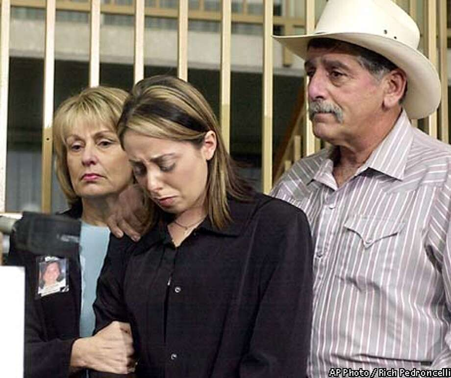 Amy Rocha, 21, center, sister of Laci Peterson, is comforted by her parents, Sharon, and Dennis Rocha, following her remarks during a news conference held in Modesto, Calif., Friday, Jan. 24, 2003. On the one-month anniversary of her disappearnce, the family begged for information about her, and declared their lack of support for Laci's husband Scott Peterson.(AP Photo/Rich Pedroncelli) Photo: RICH PEDRONCELLI