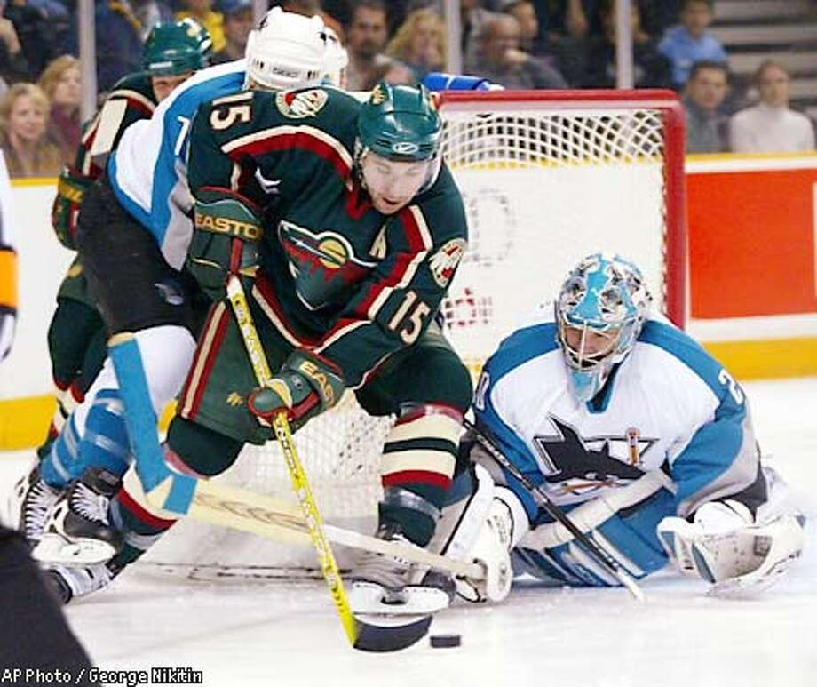 Minnesota Wild's Andrew Brunette (15) moves the puck near the goal defended by San Jose Sharks goalie Evgeni Nabokov on Saturday, Jan. 25, 2003, in San Jose, Calif. (AP Photo/George Nikitin) Photo: GEORGE NIKITIN