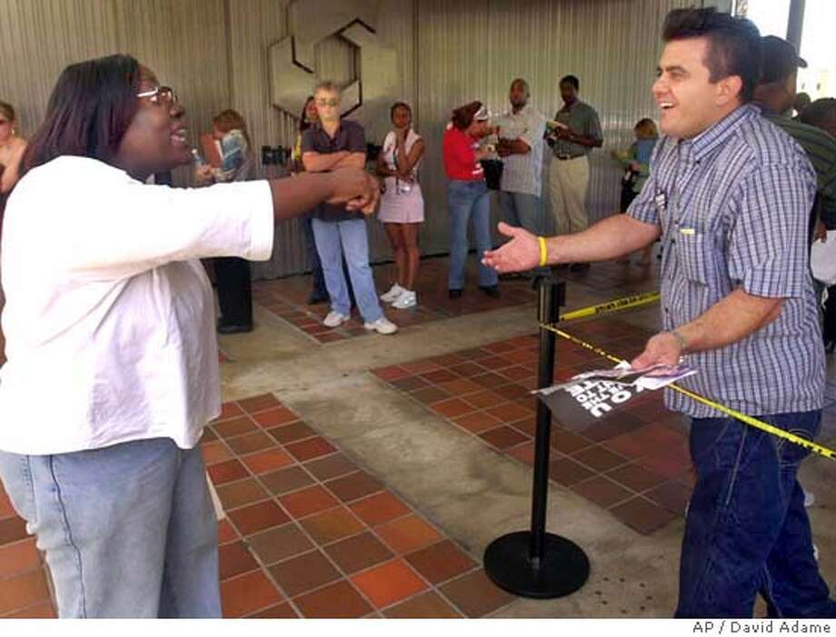 Kerry campaigner Caroline Joseph, left, argues with Bush supporter Nick Stavros, right, over policy while Stavros waits in line to early vote Monday, Nov. 1, 2004 at the Stephen P. Clark Government center in downtown Miami. This is one of only two early voting centers still open in Miami-Dade county. (AP Photo/David Adame) Photo: DAVID ADAME