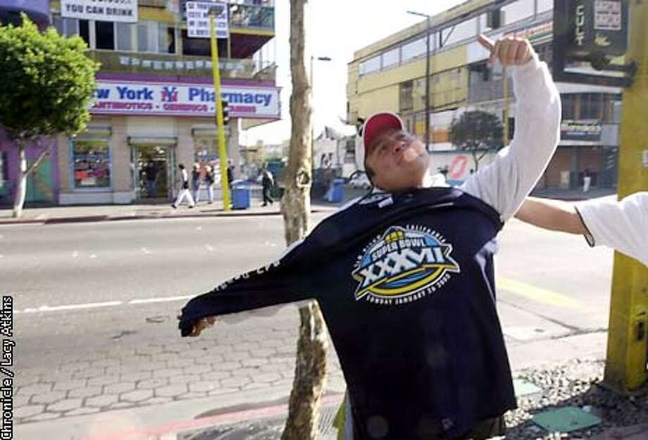 Alberto Castan, 27, shows off a knock off Super Bowl t-shirt, for sale from a next door venue, to tourist, from the street in Tijuana, as they sit upstairs having lunch, Friday Jan 24,03.  SAN FRANCISCO CHRONICLE/LACY ATKINS Photo: LACY ATKINS