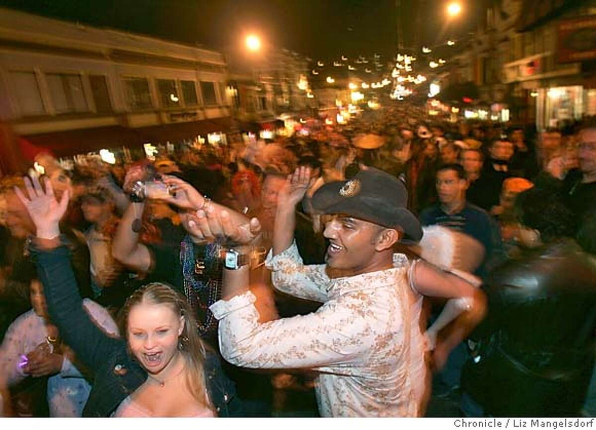 castro113_lm.JPG Event on 10/31/04 in San Francisco. Ryan Meshband, cowboy hat center, dances in the middle of castro street. He came all the way from Australia to celebrate halloween in the Castro. The Castro on halloween night. Liz Mangelsdorf / The Chronicle MANDATORY CREDIT FOR PHOTOG AND SF CHRONICLE/ -MAGS OUT Metro#Metro#Chronicle#11/1/2004#ALL#5star-dot##0422443363