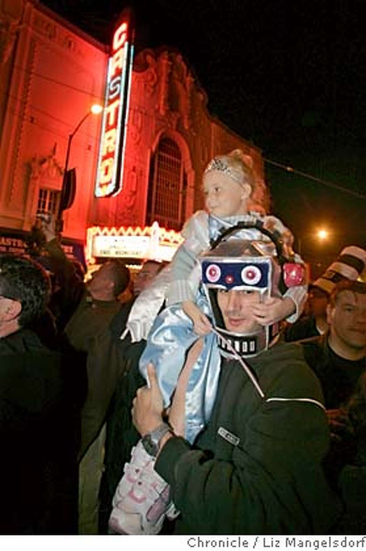 castro039_lm.JPG Event on 10/31/04 in San Francisco. Tourist's from Paris, France, Paul Maolec and his daughter Enora Morvant, 5, walk down Castro Street, with the Castro Theater in the background. The Castro on halloween night. Liz Mangelsdorf / The Chronicle MANDATORY CREDIT FOR PHOTOG AND SF CHRONICLE/ -MAGS OUT Metro#Metro#Chronicle#11/1/2004#ALL#5star-dot##0422443385