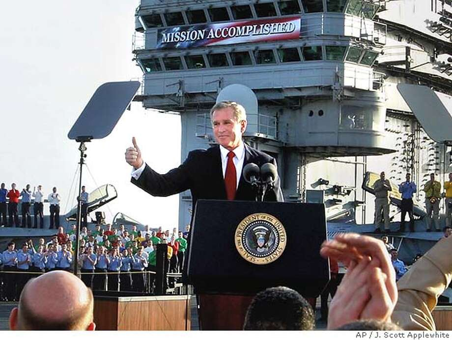 "** FILE ** President Bush flashes a ""thumbs-up"" after declaring the end of major combat in Iraq as he speaks aboard the aircraft carrier USS Abraham Lincoln off the California coast, in this May 1, 2003 file photo. One year later Bush and his advisers are struggling with the complexities of escalating violence in Iraq and a burgeoning American death toll. ""Mission accomplished"" is looking more like mission impossible. (AP Photo/J. Scott Applewhite, File) Photo: J. SCOTT APPLEWHITE"
