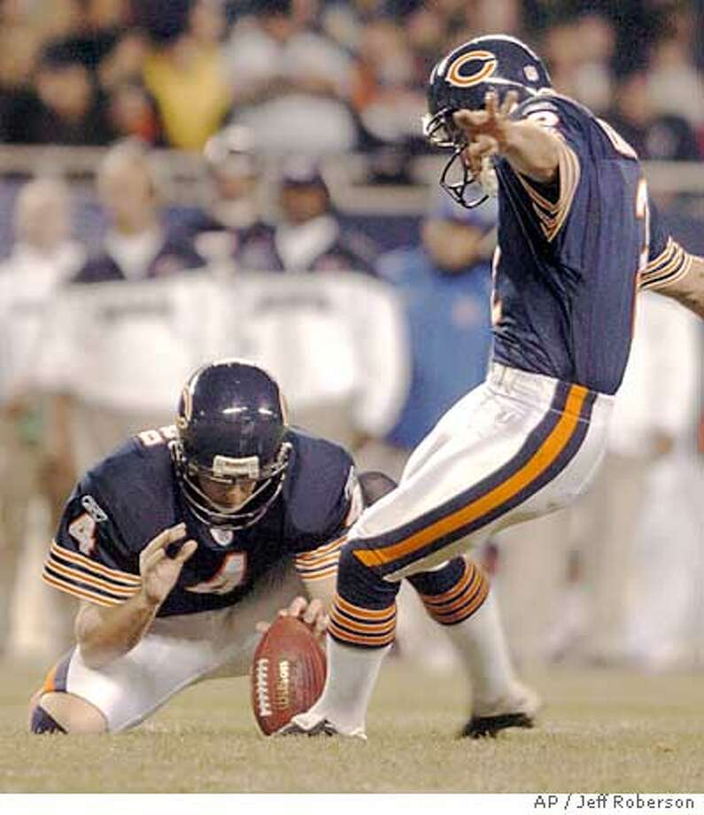 Chicago Bears kicker Paul Edinger, right, hits a 27-yard field goal as Brad Maynard, left, holds during the fourth quarter against the San Francisco 49ers, Sunday night, Oct. 31, 2004, in Chicago. The field goal gave the Bears the lead and helped them to a 23-13 win. (AP Photo/Jeff Roberson) Ran on: 11-01-2004  Paul Edinger drills a 27-yard field goal as Brad Maynard holds for him. Edinger kicked three field goals. Photo: JEFF ROBERSON