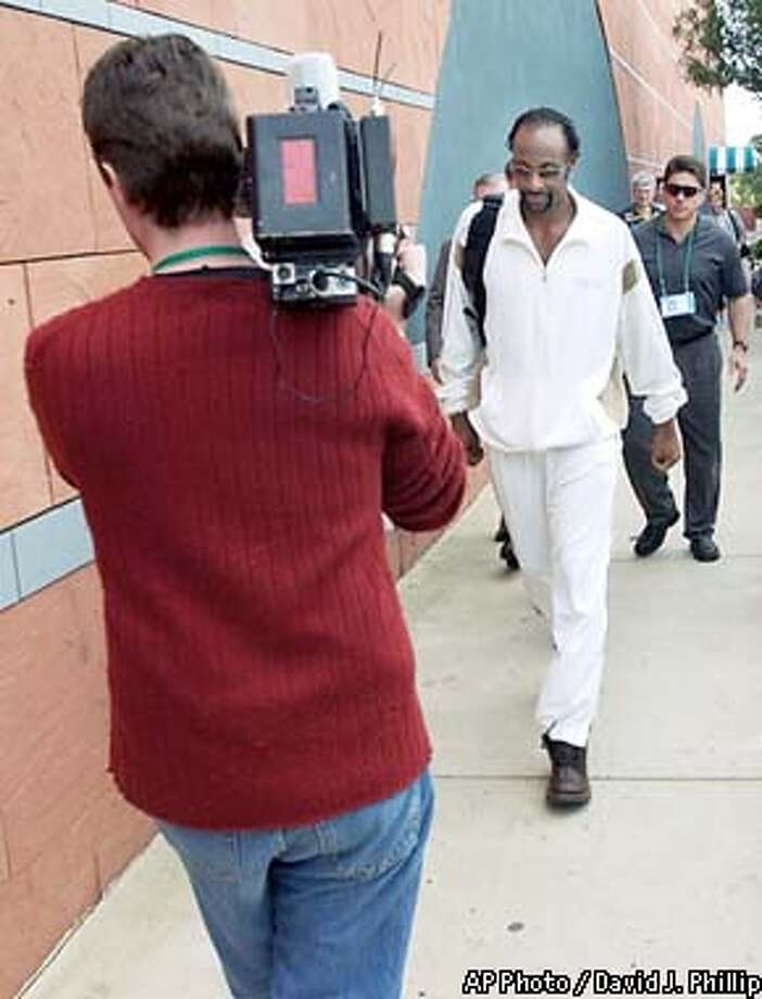 A videographer backs up as he attempts to film Oakland Raiders' Jerry Rice walking outside the team hotel in San Diego Wednesday, Jan. 22, 2003. The Oakland Raiders will meet the Tampa Bay Buccaneers in Super Bowl XXXVII on Sunday. (AP Photo/David J. Phillip) Photo: DAVID J PHILLIP