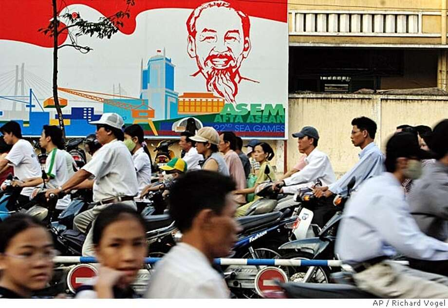 **ADVANCE FOR SUNDAY, APRIL 24** Vietnamese commuters make their way through rush hour traffic past a billboard with the portrait of former communist leader Ho Chi Minh, in Ho Chi Minh City, formerly Saigon, March 23, 2005. Three decades after the war, Vietnam has emerged from war, poverty and isolation, poised to ride an economic wave triggered by the country's decision to replace crumbling communist doctrines with free-market reforms. (AP Photo/Richard Vogel) HFR 04-24-05. ADVANCE FOR SUNDAY, APRIL 24. Photo: RICHARD VOGEL