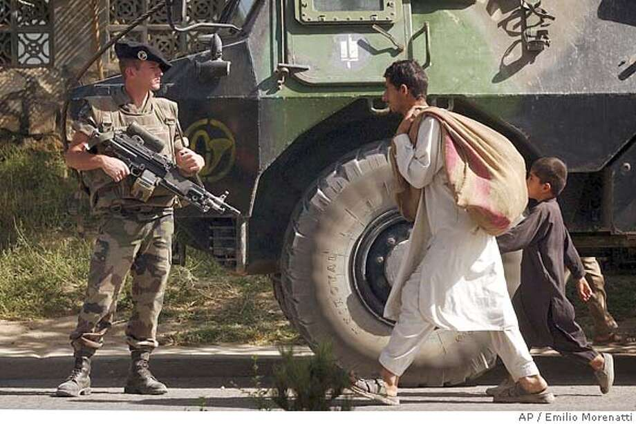 A French soldier from International Security Assistance Force keeps the guard at a checkpoint in a residential area of Kabul, Afghanistan's capital, on Saturday, Oct. 30, 2004. Afghan forces and NATO troops have mounted extra patrols and roadblocks since unidentified armed men on Thursday kidnapped a Filipino diplomat and two UN workers - Kosovan Shqipe Habibi and Annetta Flanigan from Northern Ireland. The three worked for a joint UN-Afghan commission overseeing landmark presidential elections. (AP Photo/Emilio Morenatti) Photo: EMILIO MORENATTI