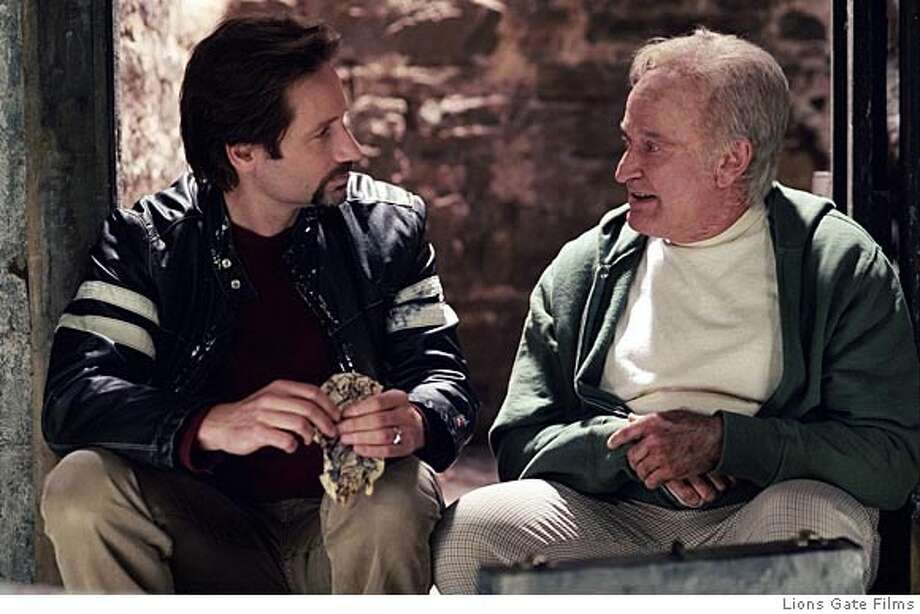 """In this photo provided by Lions Gate Films, Tom Warshaw (David Duchovny) is trying to make sense of his troubled adult life by reflecting upon his extraordinary childhood with his best friend Pappas (Robin Williams), a mentally challenged janitor in """"House of D."""" (AP Photo/Lions Gate Films)"""