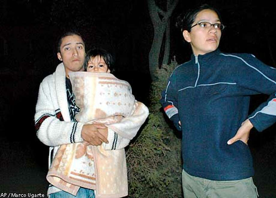 Mexico City residents stand outside their homes following a 7.6 earthquake in Mexico City Tuesday, Jan. 21, 2003. The national seismological service calculated the quake's magnitude at 7.6 and said struck at 8:07 p.m. on the coast of Colima, a small state which includes the port city of Manzanillo, roughly 500 kilometers (300 miles) west of Mexico City.(AP Photo/Marco Ugarte) Photo: MARCO UGARTE