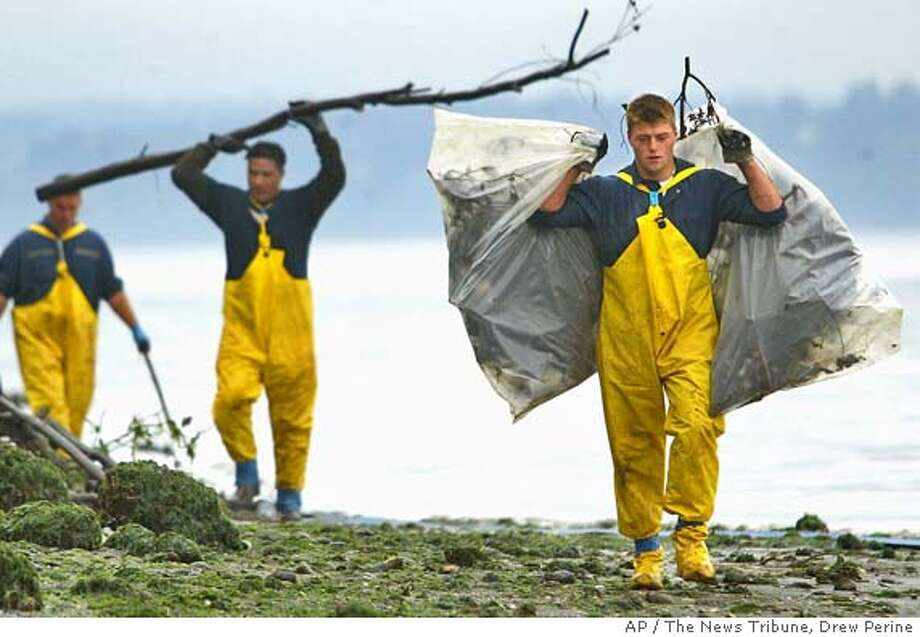 Zack O'Leary, right, carries bags filled with oil-covered wood debris down a Vashon Island, Wash., beach near Neill Point Friday, Oct. 15, 2004. O'Leary and other contract labor working for National Response Corporation, spent the day cleaning one of the most soiled beaches affected by an oil spill. (AP Photo/The News Tribune, Drew Perine) Nation#MainNews#Chronicle#10/31/2004#ALL#5star##0422415698 Photo: DREW PERINE
