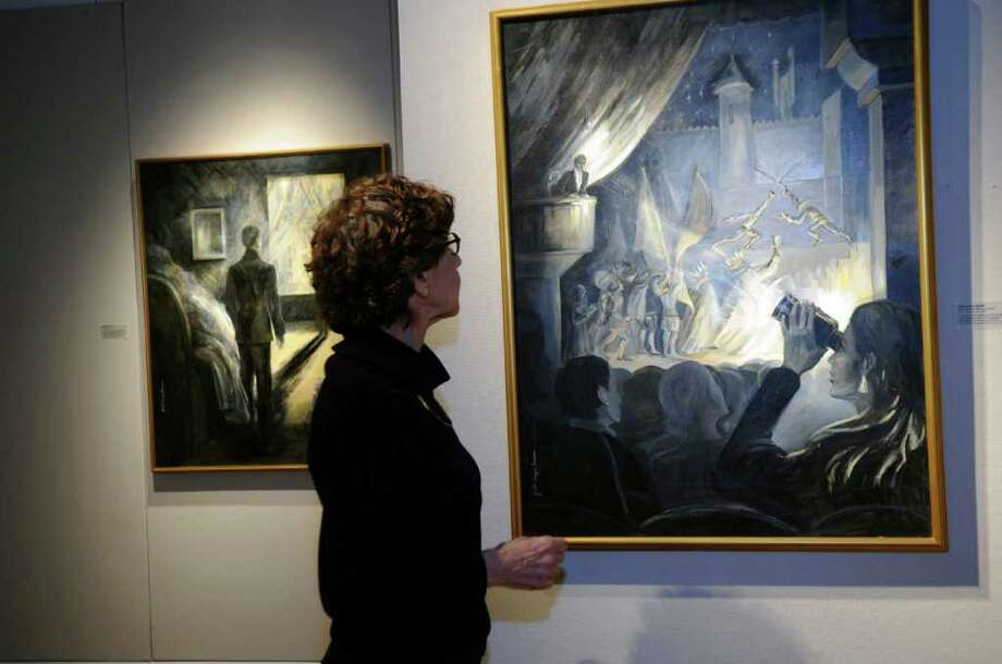 "Judith Gwyn Brown, of New York City, looks at her painting, ""In the theater: Seeing Hamlet"" part of her New York Series on view  at the Greenwich Arts Council's Bendheim Gallery at 299 Greenwich Ave. ""I paint men and women moving through the light, space and the shadows of New York."" Photo: Helen Neafsey / Greenwich Time"