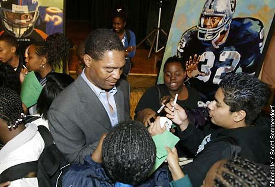 Marcus Allen signs autographs for some students at Lincoln High School in San Diego. Allen was honored at his old High School along with fellow NFL great Terrell Davis who also went to Lincoln. An eight foot tall painting of both players (in background) was donated to the school by the NFL. They will hang in the gymnasium to inspire future athletes. SCOTT SOMMERDORF / San Francisco Chronicle Photo: Scott Sommerdorf