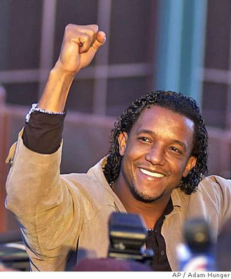 Boston Red Sox pitcher Pedro Martinez acknowledges the fans at Fenway Park in Boston, Thursday Oct. 28, 2004. The triumphant team returned home after defeating the St. Louis Cardinals 3-0 in gam4 of the World Series. (AP Photo/Adam Hunger) Photo: ADAM HUNGER