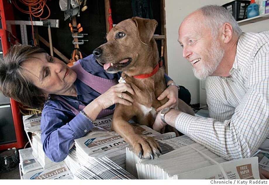 """Oakland couple Jim Decker and Vicki Kaplan have put together a monthly newspaper called """"Woofer Times"""" inspired by their dog, Woofer. This couple puts their business know-how and love of dogs into this first-of-a-kind newspaper in the Bay Area. We photograph Kim and Vicki and dog Woofer on the pile of their first edition, currently stored in the garage--it'll be distributed tomorrow. (18 Cornwall Ct. Oak. 94611) Photo taken on 4/14/05, in Oakland, CA.  By Katy Raddatz / The San Francisco Chronicle Photo: Katy Raddatz"""