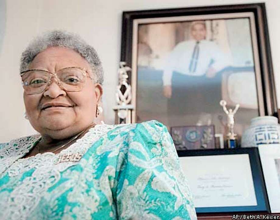 ** FILE ** Mamie Till Mobley stands before a portrait of her slain son, Emmett Till, in her Chicago home on July 28, 1995. On Monday, Jan. 6, 2003, Mobley, 81, died of heart failure in Chicago. In an Associated Press article last month, Mobley said she remained haunted by the 1955 race-motivated killing of her 14-year-old son in Mississippi where an all-white jury acquitted half brothers J.W. Milam and Roy Bryant in the black teenager's death. (AP Photo/Beth A. Keiser) Photo: BETH A. KEISER
