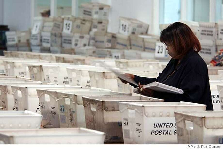 An unidentified Broward County election worker sorts absentee ballots to be mailed out Thursday, Oct. 28, 2004 at the election department's equipment center in Fort Lauderdale, Fla. With voters jamming phone lines saying they haven't received absentee ballots in the mail, elections officials planned to mail out thousands of replacement ballots. (AP Photo/J.Pat Carter) Photo: J. PAT CARTER
