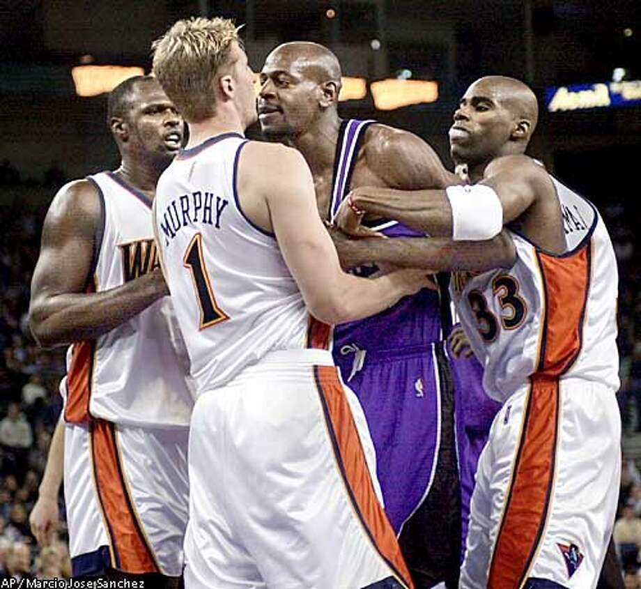 Sacramento Kings forward Keon Clark, second from right, is held back by Golden State Warriors forward Antawn Jamison, right, as he confronts forward Troy Murphy after Murphy fouled him in the first half on Monday, Jan. 20, 2003, in Oakland, Calif. (AP Photo/ Marcio Jose Sanchez) Photo: MARCIO JOSE SANCHEZ