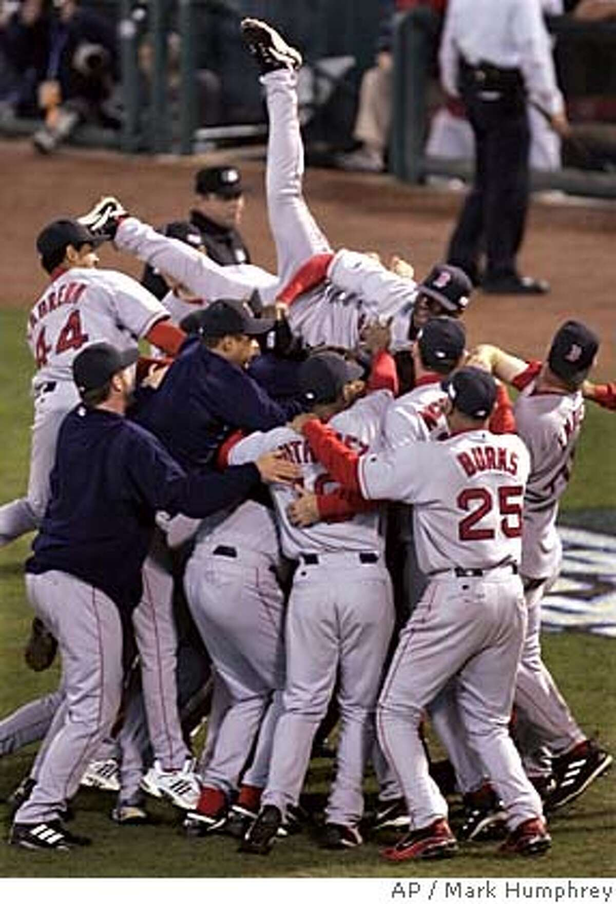 Boston Red Sox Pokey Reese jumps on top of his teammates after the Red Sox defeated the St. Louis Caridnals 3-0 in Game 4 to win the World Series at Busch Stadium in St. Louis, Wednesday, Oct. 27, 2004. (AP Photo/Mark Humphrey)